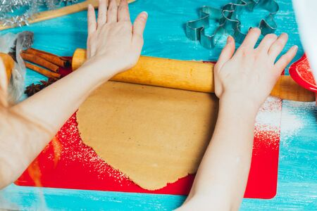 girl rolls the dough on the red board to blue wooden table. Stock Photo