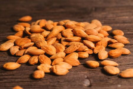 apricot kernels: Apricot kernels are scattered on the wooden background.