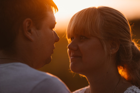 portrait of love story man and woman on the background of haystacks and sun.