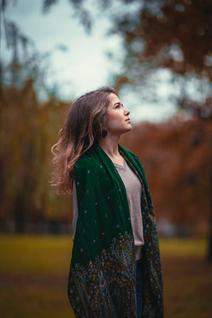 Portrait of a young girl with a green scarf on the background of autumn park photo