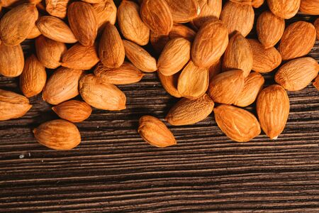 Apricot kernels are scattered on the wooden background.