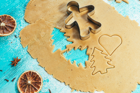 pastry cutters: metal molds on dough men tree on a blue wooden background.