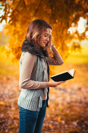 Portrait of a young girl in a fur vest and reading a book on a background of autumn park.
