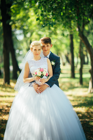 the bride and groom on the background of the park alley