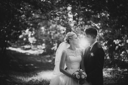 black and white photo portrait of the bride and groom on the forest background.