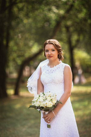 portrait of a young bride with  wedding bouquet on  park backgro
