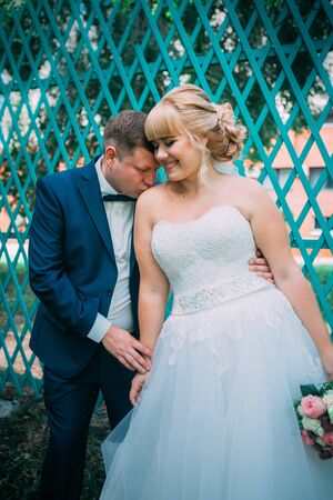bride and groom on the background of the garden fence Stock Photo