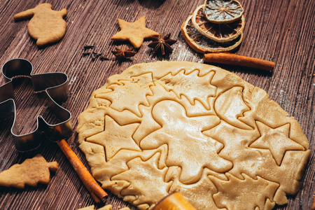 pastry cutters: Gingerbread dough with molds for baking cinnamon on dark wooden table Stock Photo