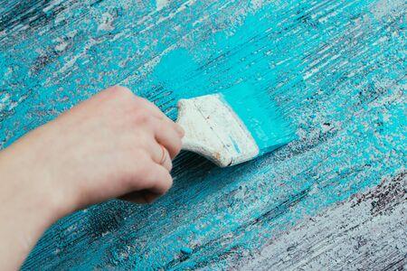 close-up hand gebruik penseel verf wit blauw op hout oppervlak Stockfoto
