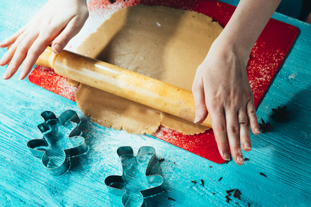 girl rolls the dough on the red board to blue wooden table Stock Photo