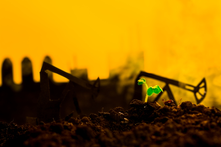 oil and gas industry: Young green plant in soil on background oil rocking machine