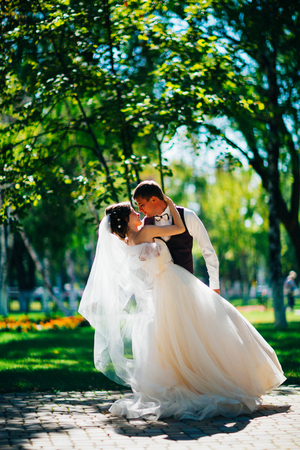 The bride and groom in the background of the park.