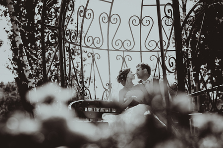the bride and groom in the gazebo in the park