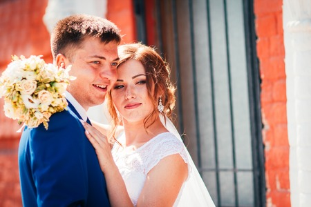 Bride and groom embracing on city background