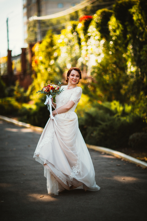 Bride on a background of trees in the park. Stock Photo