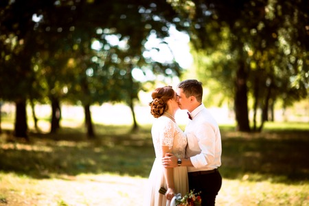 The bride and groom in the background of park trees Stock Photo