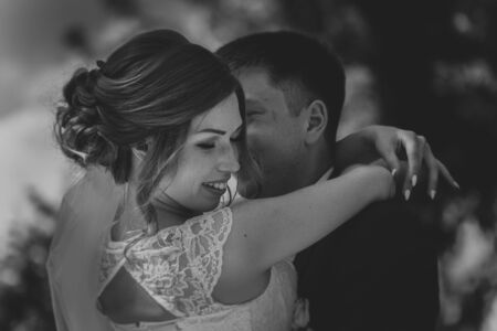 black white photo couple groom and bride on the background leaves