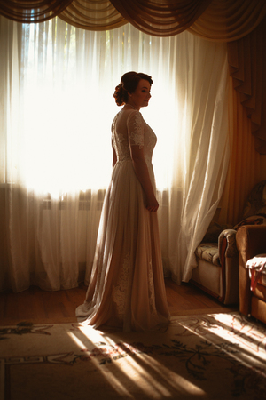 beautiful young bride near the window in full growth
