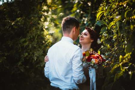 The bride and groom in the foliage of trees