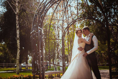 The bride and groom in the park arch