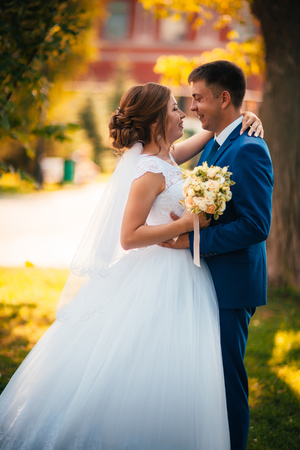 couple groom and bride against the background of orange leaves