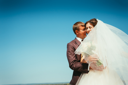 young bride and groom couple on the sky background Stock Photo
