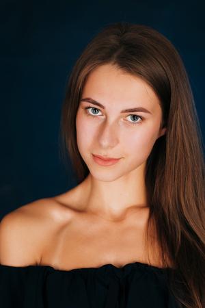 Portrait beautiful girl on a dark studio background.