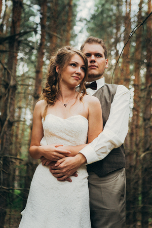 bride and groom in the forest of firs. Foto de archivo
