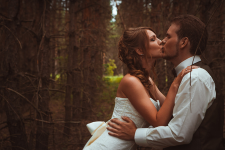 bride and groom in the forest of firs. Reklamní fotografie