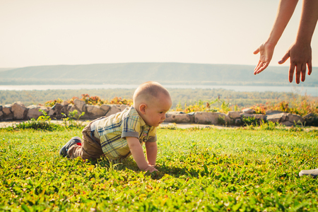 Baby boy on green grass nature background.