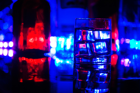 colored lighting of glasses in the night club bar.