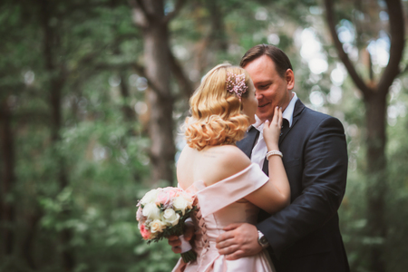 bride and groom kissing in the summer forest.