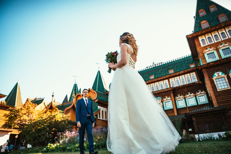 Walk young bride and groom on old house background. 스톡 콘텐츠 - 114220268
