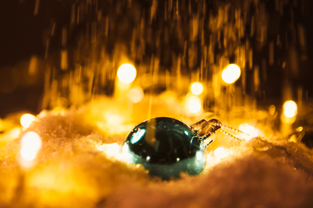 blue Christmas ball and luminous garland on the snow. Reklamní fotografie