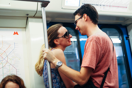 girl and guy stand in the subway.