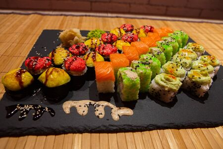 Set of rolls on a black plate with wasabi and ginger.