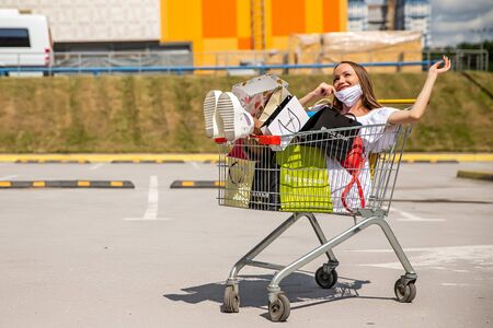girl in medical mask with purchases near the mall