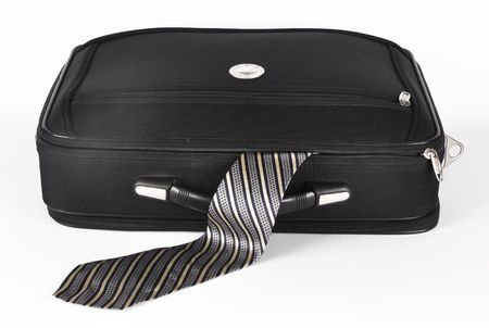 Picture of suitcase of with sticking out by a masculine tie on a white background