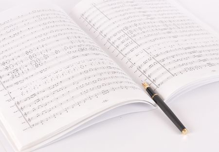 Picture of pen on a musical notebook on a white background photo