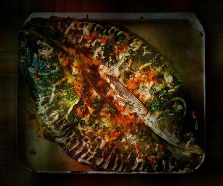 bakplaat: Opgesteld gebakken vis op het rooster. Onder kleur licht. Stockfoto