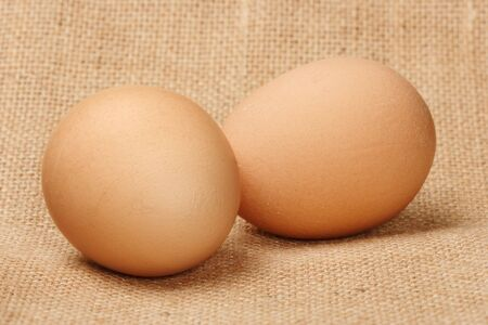yellowish: Two chicken eggs on the linen Stock Photo