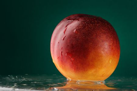 Peach on the glass table over green background Stock Photo