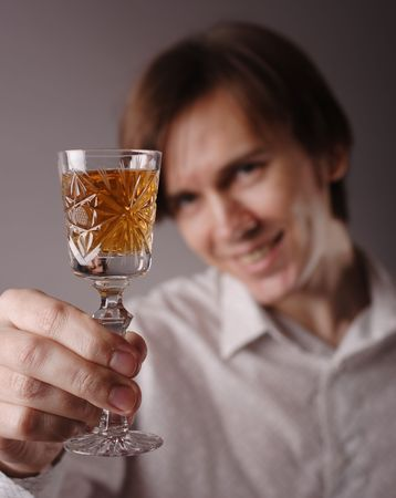 Man with glass of wine in right hand. Focus on the wineglass.