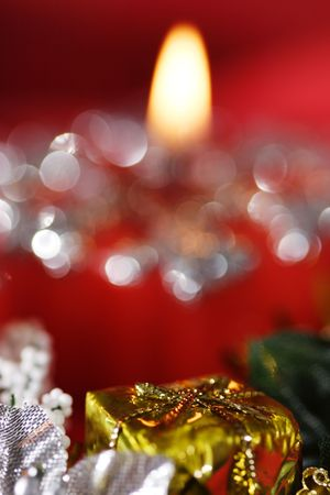 Golden gift box in front of red candle. Narrow depth of field. photo