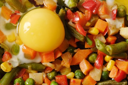 Fried eggs with vegetables on the skillet. Hot and fresh. photo