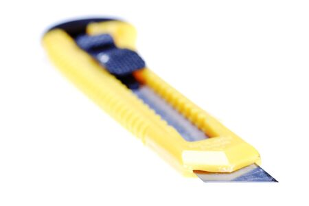 utility knife: Sharp retractable utility knife with yellow plastic handle. Isolated on the white background. Narrow depth of field.