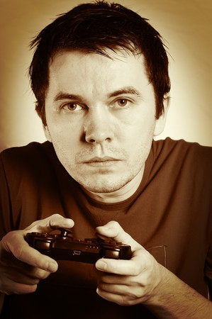videogame: Man with game pad playing videogame. Sepia tint.
