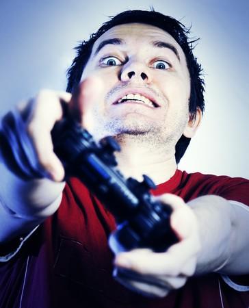 ゲーム パッドのビデオゲームをプレイを持つ男。青の色合い。