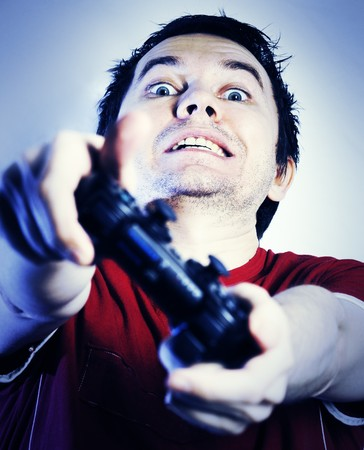 videogame: Man with game pad playing videogame. Blue tint. Stock Photo