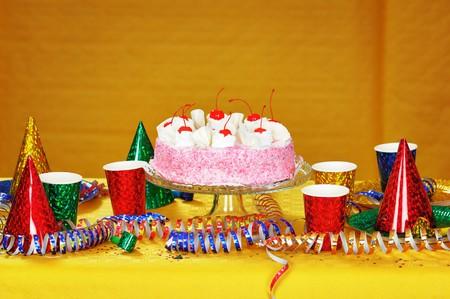 Birthday cake with red cherry. Narrow depth of field. Close-up. Orange tint. photo